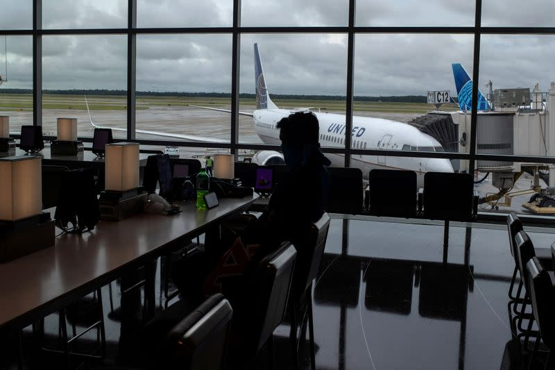 FILE PHOTO: United Airlines plane is seen in the background as a passenger sits in IAH George Bush Intercontinental Airport in Houston