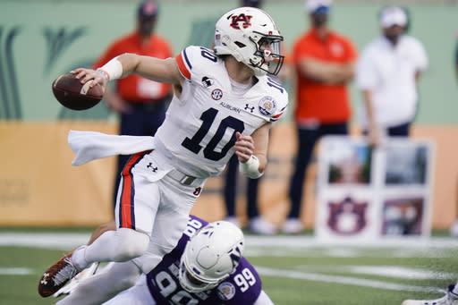 Auburn quarterback Bo Nix (10) dodges a tackle by Northwestern defensive end Earnest Brown IV (99) during the first half of the Citrus Bowl NCAA college football game, Friday, Jan. 1, 2021, in Orlando, Fla. (AP Photo/John Raoux)