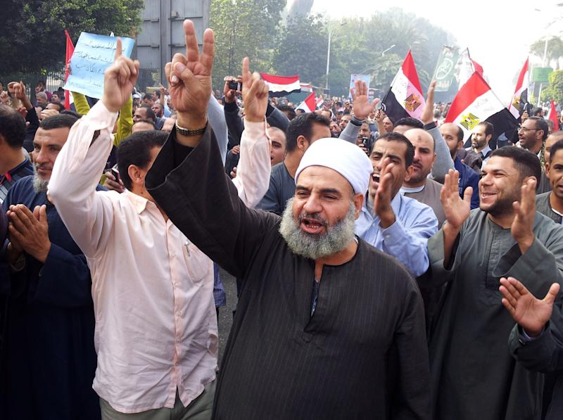 In this image made with a mobile phone camera, supporters of Egyptian President Mohammed Morsi march in Cairo, Egypt, Saturday, Dec. 1, 2012. Thousands of people waving Egyptian flags and hoisting large pictures of the president demonsteated across Egypt in support of the president. The Muslim Brotherhood, from which President Morsi hails, hopes for a large turnout at the Saturday rallies to counter opposition protests. Hundreds of thousands of people took to the streets twice this week opposing Morsi's decrees last week to grant himself sweeping powers. (AP Photo/Thomas Hartwell)