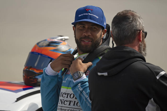 Driver Bubba Wallace gets ready to enter his car for qualifying rounds before the NASCAR Xfinity Series auto race, Saturday, Oct. 5, 2019, in Dover, Del. (AP Photo/Brien Aho)
