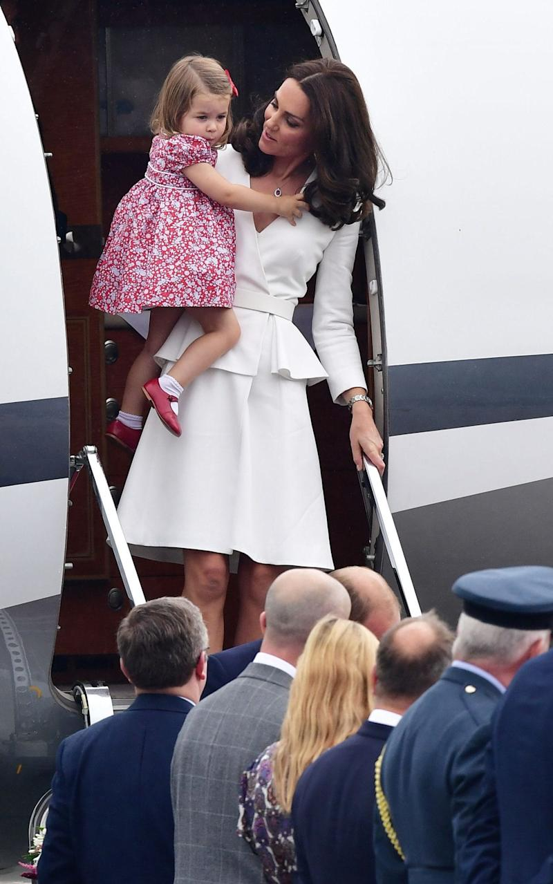 Princess Charlotte is carried down the plane's small flight of steps by her mother - Credit: Dominic Lipinski/PA