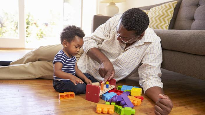 grandparent and young child playing with toys
