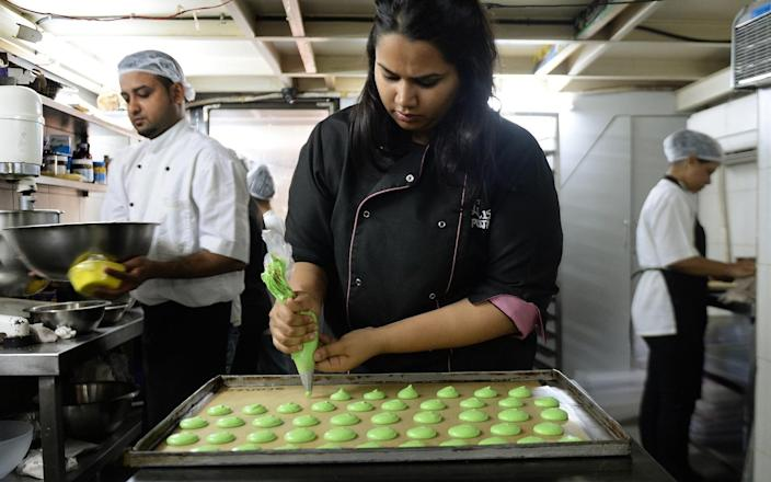 In this photograph taken on February 20, 2015, Pooja Dhingra pipes macarons at the Le15 - Patisserie bakery in Mumbai. (Photo by PARANJPE/AFP via Getty Images)