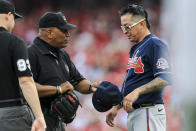MLB umpire Laz Diaz, left, inspects the hat and glove of Atlanta Braves' Jesse Chavez after the first inning of a baseball game against the Cincinnati Reds in Cincinnati, Thursday, June 24, 2021. (AP Photo/Aaron Doster)
