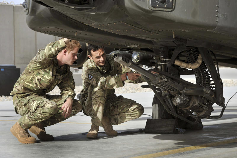 In this Friday, Sept. 7, 2012 photo made available on Sunday, Sept. 9, 2012, Britain's Prince Harry, left, examines the 30mm cannon of an Apache attack helicopter with an unidentified member of his squadron, at Camp Bastion in Afghanistan, where he starts his tour of duty as a co-pilot gunner.  The 27-year-old Army captain Prince Harry, known as Captain Harry Wales, is on his second tour of duty in Afghanistan but will go through the usual familiarization process before becoming operational and flying attack helicopters. (AP Photo / John Stillwell, Pool)