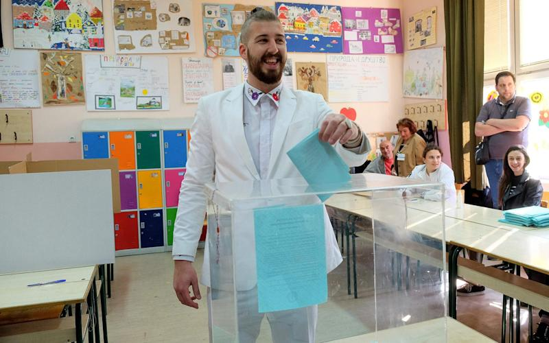 Luka Maksimovic, in character as Beli Preletacevic, casts his ballot at a polling station at Mladenovac - Credit:  VLADIMIR ZIVOJINOVIC/AFP