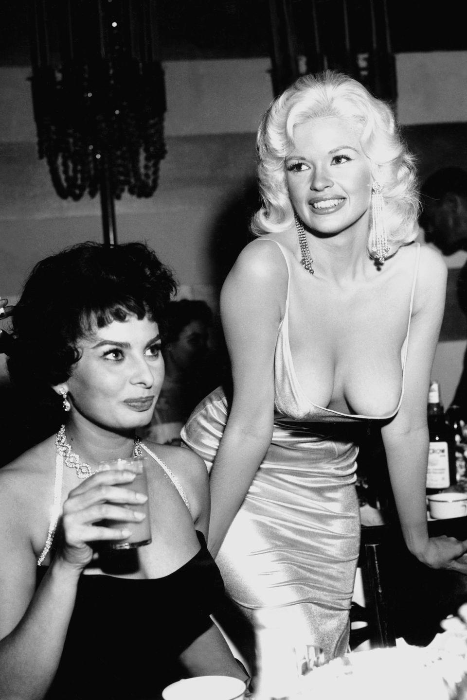 <p>Mansfield kept up with the same publicity antics that she used to grab her studio's attention years before and became known for creating a spectacle in the form of photo bombs or manufacturing wardrobe malfunctions for the press. The actress garnered a lot of attention for one photo in particular: the Sophia Loren side-eye for this revealing dress.</p>