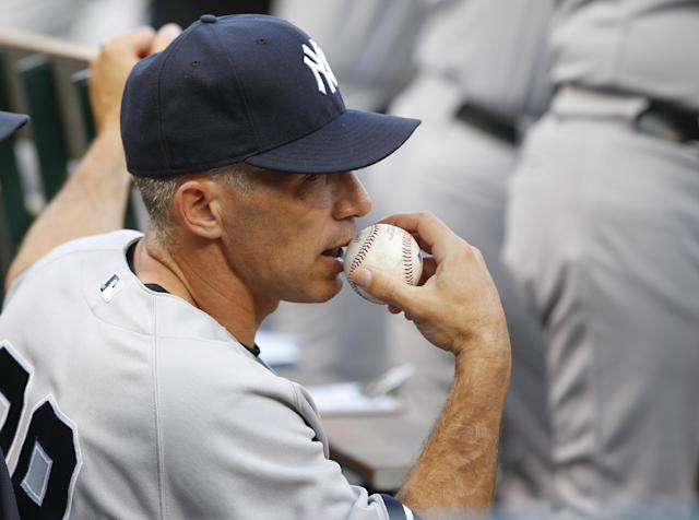 New York Yankees manager Joe Girardi watches from the dugout during the Yankees' baseball game against the Texas Rangers, Wednesday, July 24, 2013, in Arlington, Texas. (AP Photo/Jim Cowsert)