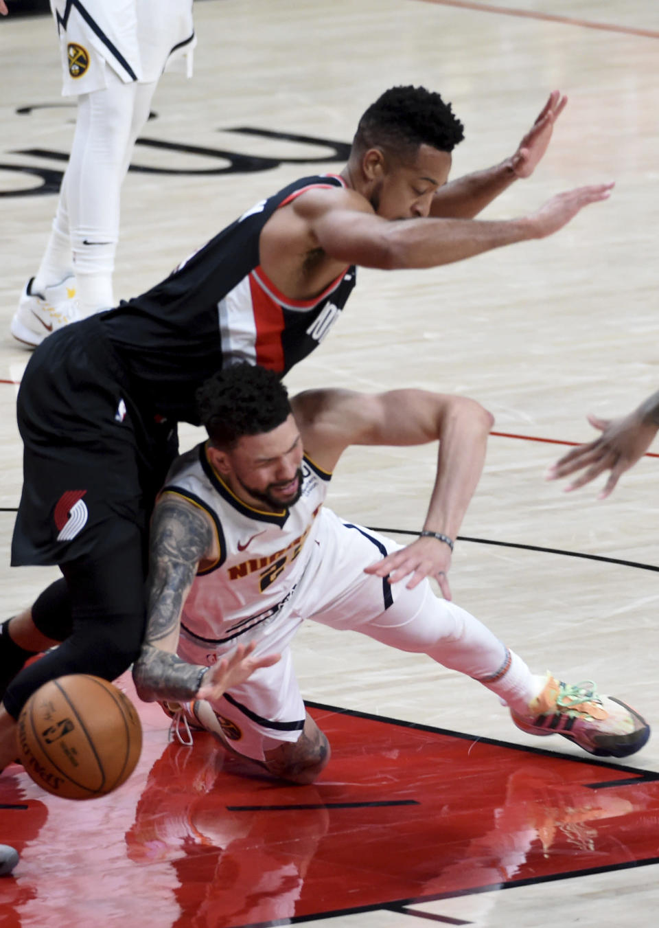 Denver Nuggets guard Austin Rivers, right, falls to the court as Portland Trail Blazers guard CJ McCollum, left, defends during the first half of Game 4 of an NBA basketball first-round playoff series in Portland, Ore., Saturday, May 29, 2021. McCollum was called for a foul on the play. (AP Photo/Steve Dykes)