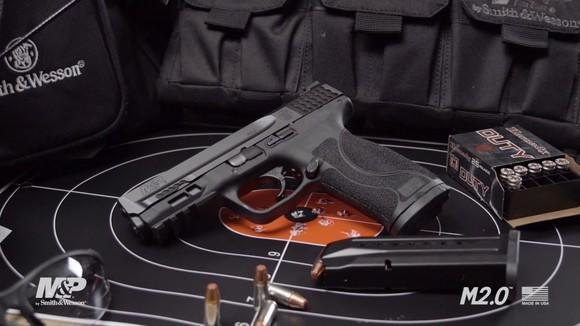 A Smith & Wesson M&P 9 Shield 2.0 with a box of ammunition on top of a target.