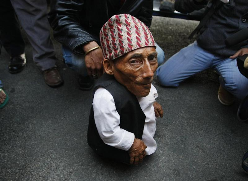 Nepalese Chandra Bahadur Dangi, 72, who says he's only 22 inches (56 centimeters) tall arrives at the airport in Katmandu, Nepal, Wednesday, Feb. 22, 2012. Guinness World Records officials will be in Nepal this weekend to measure Dangi who hopes to be named the world's shortest man. Dangi is hoping to snatch the title of the world's shortest man from Junrey Balawing of the Philippines, who is 23.5 inches (60 centimeters) tall. (AP Photo/Binod Joshi)