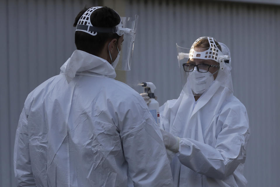 A healthcare worker has his protective suit disinfected at a sampling station for COVID-19 in Prague, Czech Republic, Monday, Sept. 21, 2020. The country coped well with the first wave of the coronavirus infections in the spring but has been facing a record surge of the new confirmed cases last week. (AP Photo/Petr David Josek)