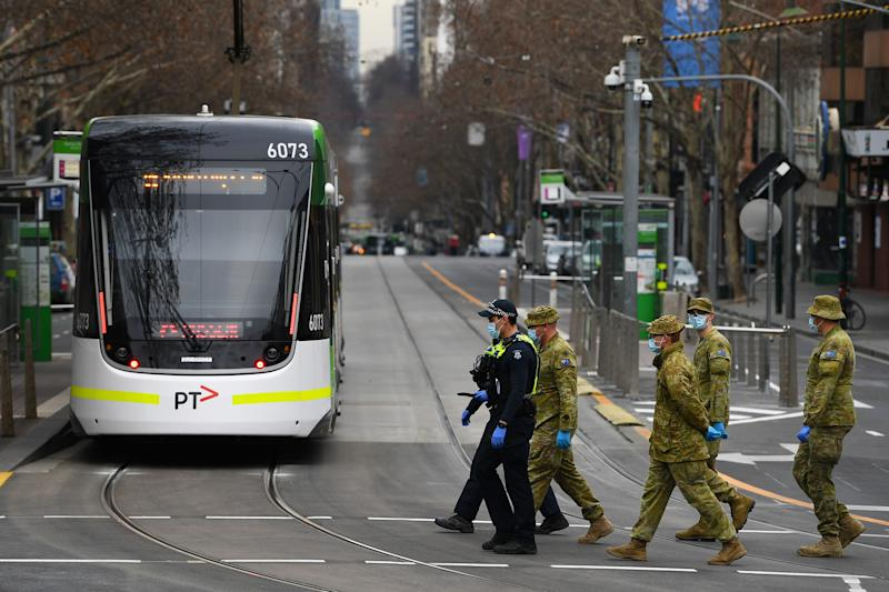 Victorian Police officers and ADF personnel are seen along Bourke street in Melbourne.