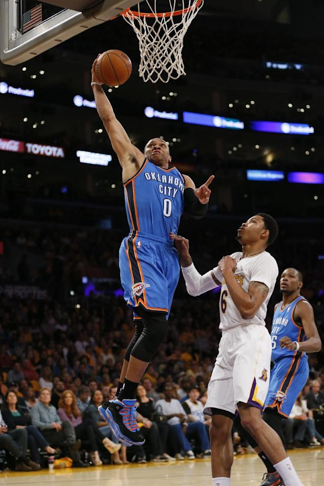 Oklahoma City Thunder point guard Russell Westbrook, left, goes to the hoop over Los Angeles Lakers shooting guard Kent Bazemore during the first half of an NBA basketball game in Los Angeles, Sunday, March 9, 2014. (AP Photo/Danny Moloshok)