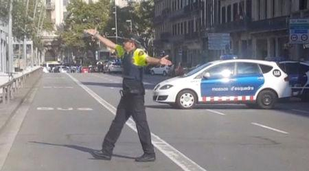 A still image from video shows a police officer gesturing while walking across a road after a van crashed into people in the centre of Barcelona