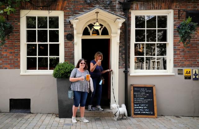 Two women walk out of The Old Vine pub with their takeaway beer in Winchester, southern England (Picture: Getty)