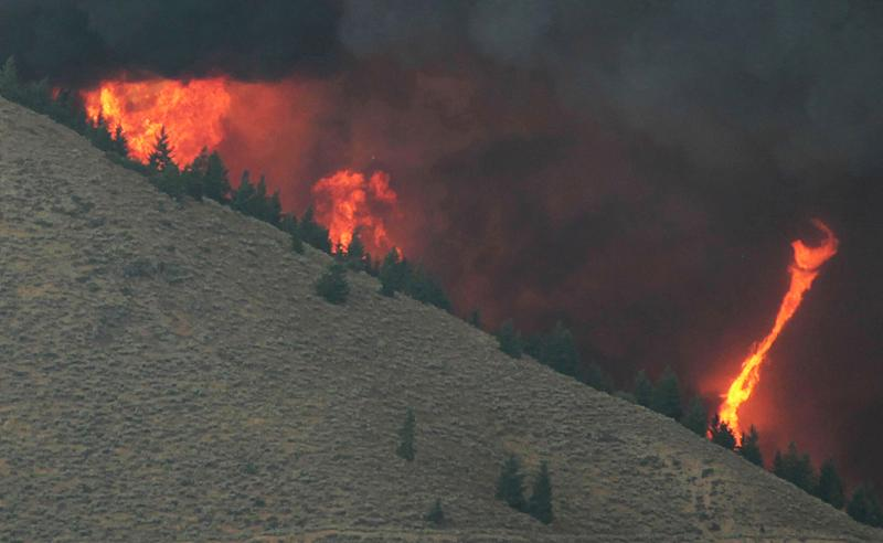 A fire whirl highlights the eratic wind conditions from the 64,000 acre Beaver Creek Fire on Friday, Aug., 16, 2013 north of Hailey, Idaho. A number of residential neighborhoods have been evacuated because of the blaze.(AP Photo/Times-News, Ashley Smith) MANDATORY CREDIT