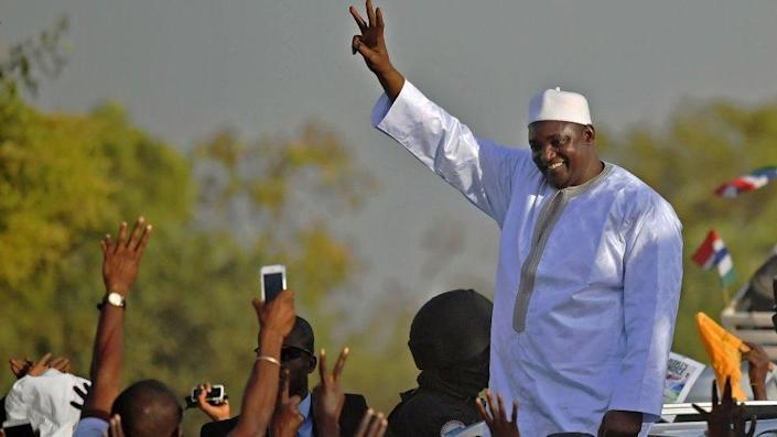 Gambia's President Adama Barrow waves to supporters as he leaves the airport in Banjul on January 26, 2017, after returning from Senegal