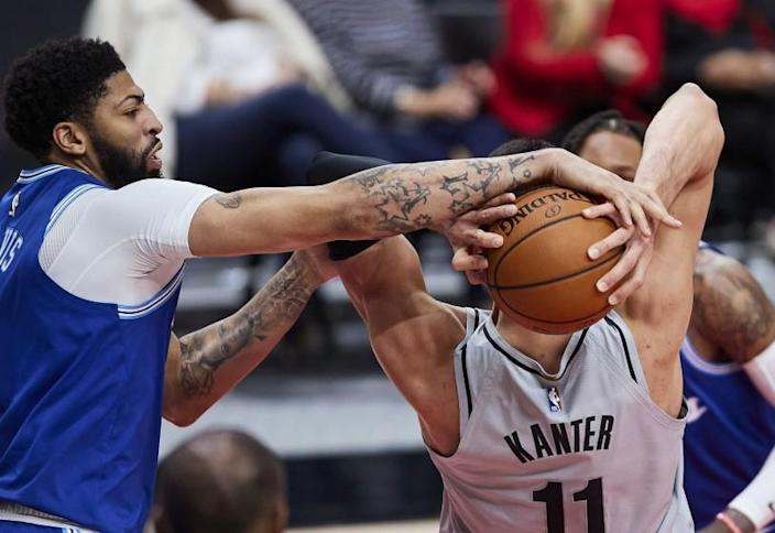 Los Angeles Lakers forward Anthony Davis, left, reaches for the ball held by Portland Trail Blazers center Enes Kanter during the second half of an NBA basketball game in Portland, Ore., Friday, May 7, 2021. (AP Photo/Craig Mitchelldyer)