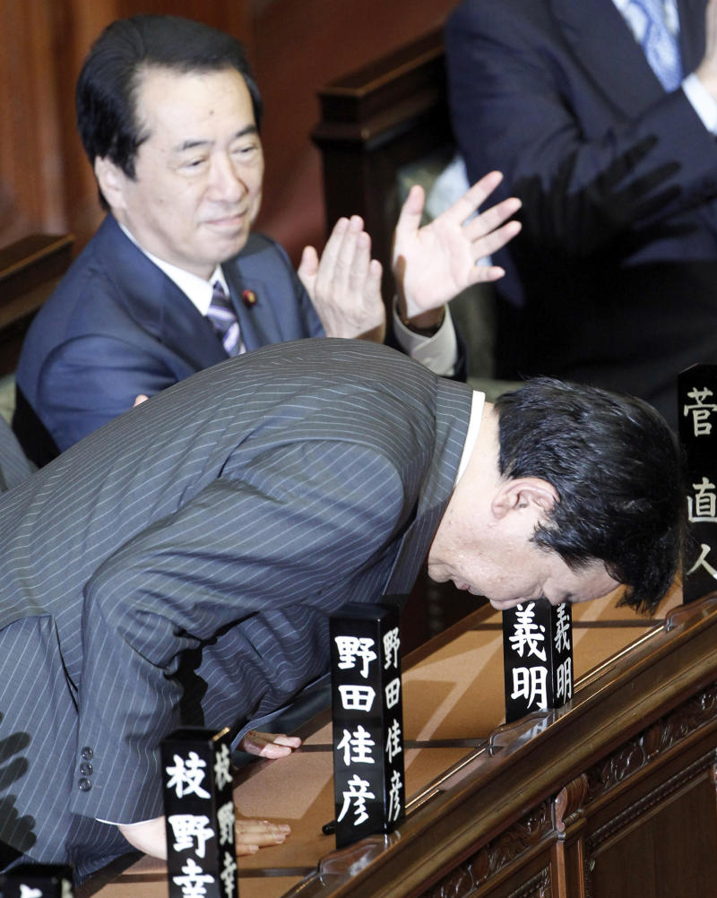 FILE - In this Aug. 30, 2011 file photo, Yoshihiko Noda, new president of the ruling Democratic Party of Japan, bows after Japan's lower house elected Noda as the country's new prime minister as outgoing Prime Minsiter Naoto Kan applauds at the lower house of Parliament in Tokyo.  Like his five predecessors, Japan's new prime minister is unlikely to last more than a year unless he can unify his divided party and convince the opposition to work together toward solutions to the country's myriad problems. (AP Photo/Koji Sasahara, File)
