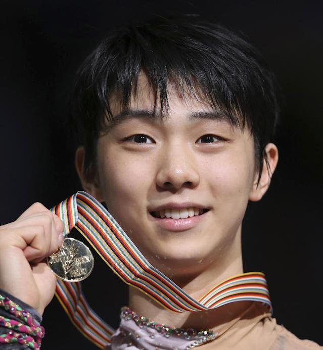 Gold medalist Yuzuru Hanyu of Japan poses for photographers with his medal during an awarding ceremony for the men's figure skating of the World Figure Skating Championships in Saitama near Tokyo, Friday, March 28, 2014. Hanyu barely topped the free skate to become the first man in 12 years on Friday to win the Olympic and world figure skating titles in the same year. (AP Photo/Koji Sasahara)