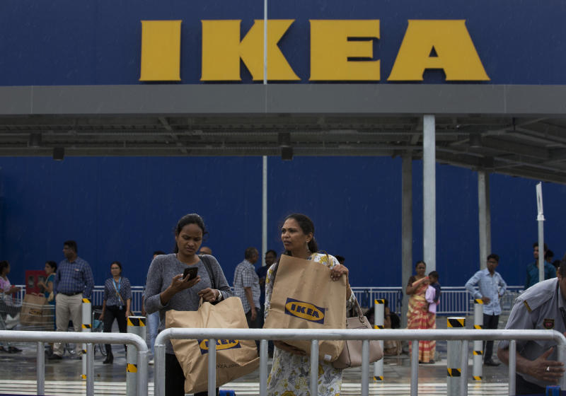 Indian customers return after shopping at IKEA's first store in India as it opened in Hyderabad, India, Thursday, Aug.9, 2018. Swedish home furnishings giant IKEA opened its first store in India on Thursday, five years after it received approval to invest in the country's single-brand retail sector. (AP Photo/Mahesh Kumar A.)