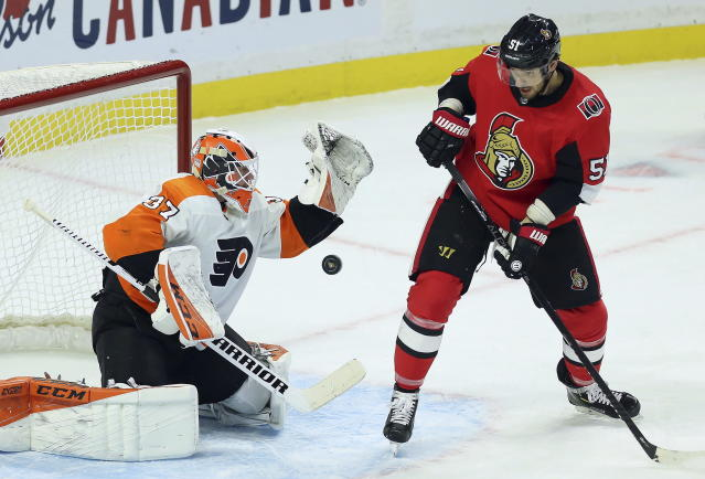 Philadelphia Flyers goaltender Brian Elliott (37) makes a save as Ottawa Senators center Artem Anisimov (51) looks on during the first period of an NHL hockey game, Saturday, Dec. 21, 2019, in Ottawa, Ontario. (Fred Chartrand/The Canadian Press via AP)