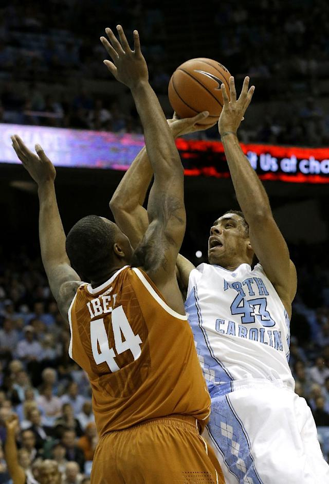 Texas' Prince Ibeh (44) defends North Carolina's James Michael McAdoo (43) during the first half of an NCAA college basketball game in Chapel Hill, N.C., Wednesday, Dec. 18, 2013. (AP Photo/Gerry Broome)