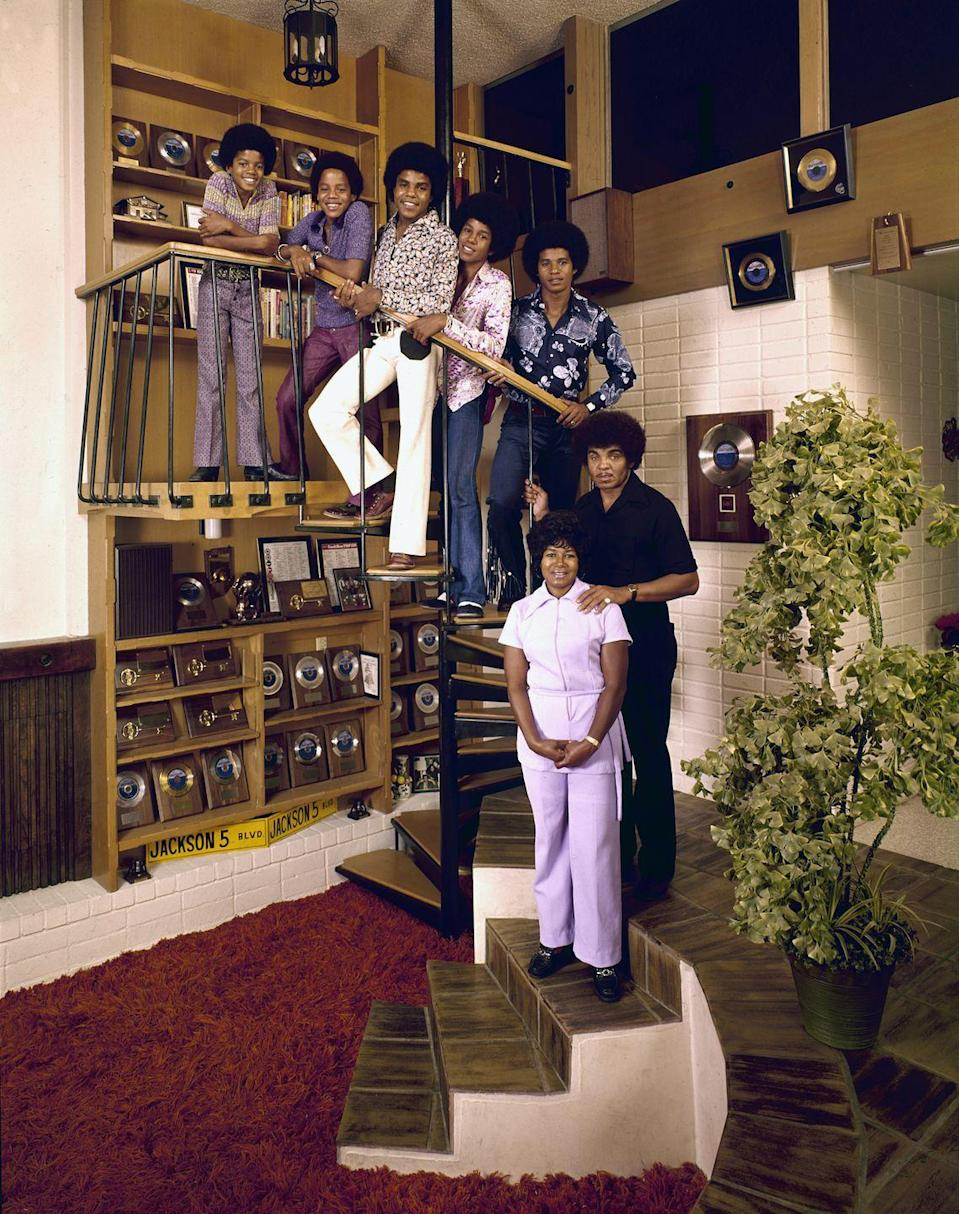 <p>The singing group poses amongst their gold records and memorabilia at home, with their parents Joe and Katherine Jackson, in 1971.</p>