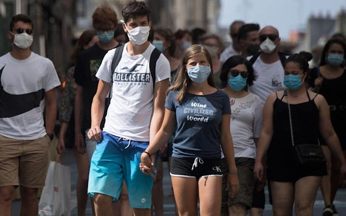 People wear protective face masks as they stroll along a street in Nantes - LOIC VENANCE/AFP