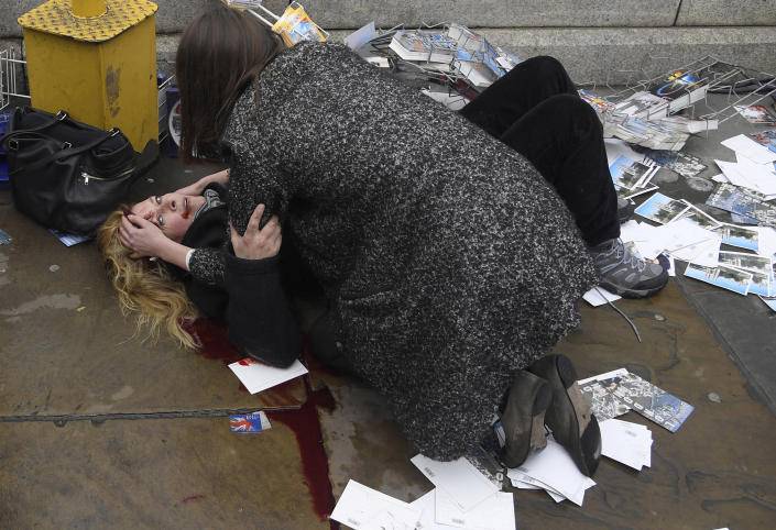 <p>Witnessing the Immediate Aftermath of an Attack in the Heart of London: A passerby comforts U.S. tourist Melissa Cochran, injured in an attack on pedestrians at Westminster Bridge in London, UK, March 22, 2017. Melissa survived, but lost her husband, Kurt, in the attack.<br>On March 22, Khalid Masood drove a rented SUV along the sidewalk of Westminster Bridge, near the British Houses of Parliament in central London. Three people were killed instantly, and two more died in the days after the attack; at least 40 were injured.<br>Armed with two knives, Masood left the car and attempted to enter the grounds of parliament, where he fatally stabbed one of the policemen who tried to stop him, before being shot and killed.<br>Born Adrian Russell Elms in Kent, UK, Masood changed his name when he converted to Islam. Although ISIS claimed responsibility for the attack the following day, police investigating found no evidence of any links between Masood and either ISIS or al-Qaeda. (Photo: Toby Melville/Reuters) </p>