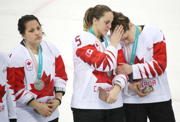 Canada defenseman Lauriane Rougeau, middle, consoles Canada forward Rebecca Johnston, right, after receiving their silver medals, Brigette Lacquette is on the left.