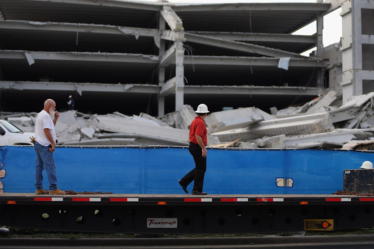 DORAL, FL - OCTOBER 10:  Construction workers look on from a flat bed truck at the rubble of a four-story parking garage that was under construction and collapsed at the Miami Dade College's West Campus on October 10, 2012 in Doral, Florida.  Early reports indicate that one person was killed, at least seven people injured and one is still trapped.  (Photo by Joe Raedle/Getty Images)