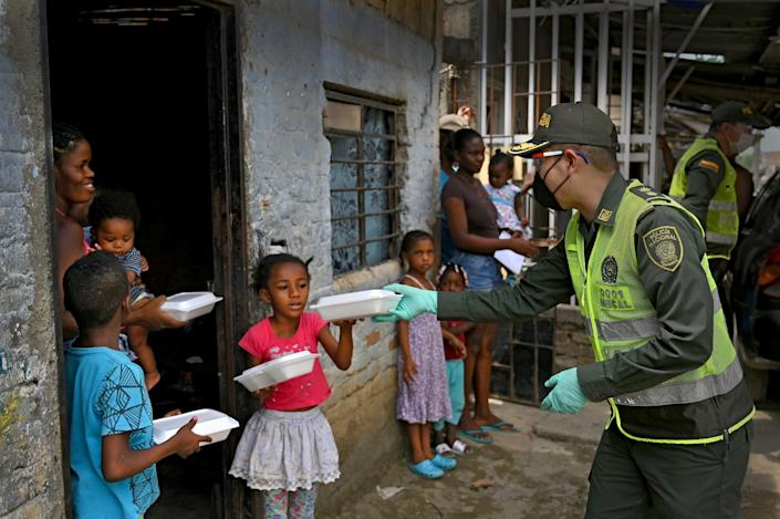 "Police Chief Manuel Vásquez, right, delivers lunch boxes to a family Wednesday in the Aguablanca district of Cali, Colombia. <span class=""copyright"">(Luis Robayo / AFP / Getty Images)</span>"