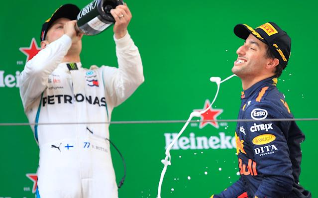 Formula One F1 - Chinese Grand Prix - Shanghai International Circuit, Shanghai, China - April 15, 2018 Red Bull's Daniel Ricciardo celebrates with champagne after winning the race as Mercedes' Valtteri Bottas drinks REUTERS/Aly Song
