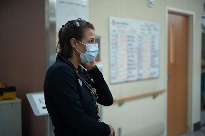 """Dr. Meghan McInerney, a pulmonologist and intensivist, who also is the director of the ICU at Saint Alphonsus Regional Medical Center, stands in front of """"the Board,"""" which is full of names of patients with COVID-19."""