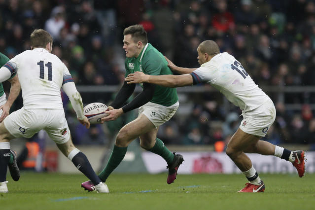 Ireland's Jacob Stockdale, center, passes the ball before being tackled by England's Elliot Daly, left, and Jonathan Joseph during the Six Nations rugby union match between England and Ireland at Twickenham stadium in London, Saturday, March 17, 2018. (AP Photo/Tim Ireland)