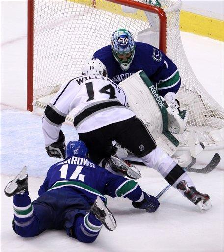 Vancouver Canucks right wing Alex Burrows (14) tries to stop Los Angeles Kings right wing Justin Williams (14) from getting a shot on Vancouver Canucks goalie Roberto Luongo (1) during first period of Game 2 of first-round NHL Stanley Cup playoff hockey action at Rogers Arena in Vancouver, British Columbia, Friday, April, 13, 2012. (AP Photo/The Canadian Press, Jonathan Hayward)