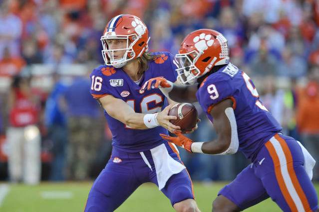 Clemson's Trevor Lawrence, left, hands the ball off to Travis Etienne during the first half of an NCAA college football game against Wofford, Saturday, Nov. 2, 2019, in Clemson, S.C. (AP Photo/Richard Shiro)