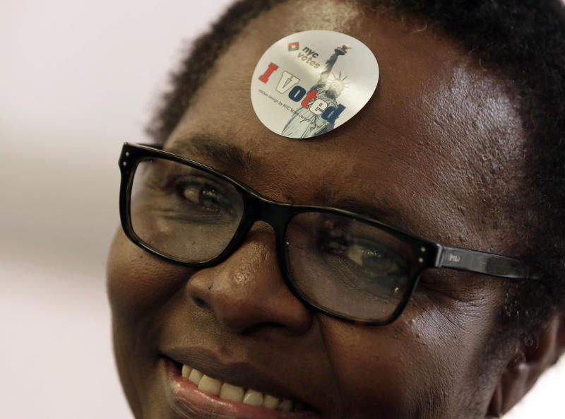 """Poll Worker Edith Maduakolam wears an """"I Voted"""" sticker on her forehead as she scans ballots at Public School 6, in New York, Tuesday Nov. 5, 2013. The casting of ballots Tuesday signals the beginning of New York City's farewell to Mayor Michael Bloomberg, who has helped shape the nation's biggest city for 12 years, largely setting aside partisan politics as he led with data-driven beliefs and his vast fortune.(AP Photo/Richard Drew)"""