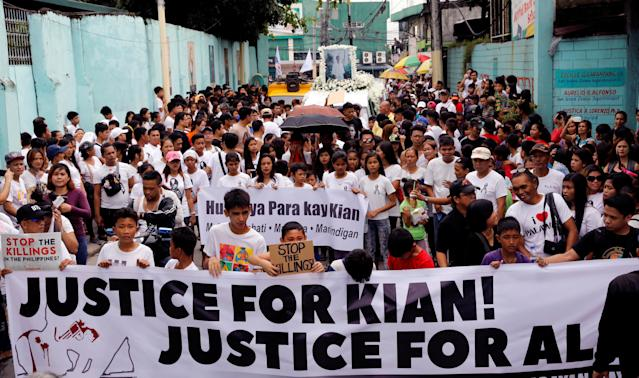 Mourners display a streamer during a funeral march for Kian delos Santos, a 17-year-old student who was killed in Caloocan, Philippines, on Aug. 26. (Erik de Castro / Reuters)