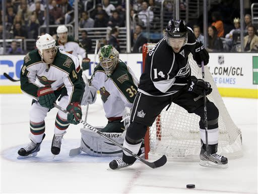 Los Angeles Kings' Justin Williams(14) controls the puck as Minnesota Wild's Clayton Stoner and goalie Darcy Kuemper, of Finland, watch during the second period of an NHL hockey game in Los Angeles, Thursday, April 4, 2013. (AP Photo/Jae C. Hong)