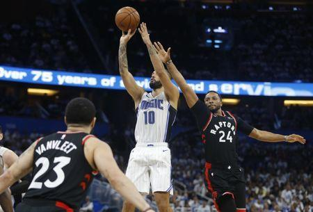Apr 19, 2019; Orlando, FL, USA; Orlando Magic guard Evan Fournier (10) shoots between Toronto Raptors forward Norman Powell (24) and guard Fred VanVleet (23) during the second half of game three of the first round of the 2019 NBA Playoffs at Amway Center. Mandatory Credit: Reinhold Matay-USA TODAY Sports