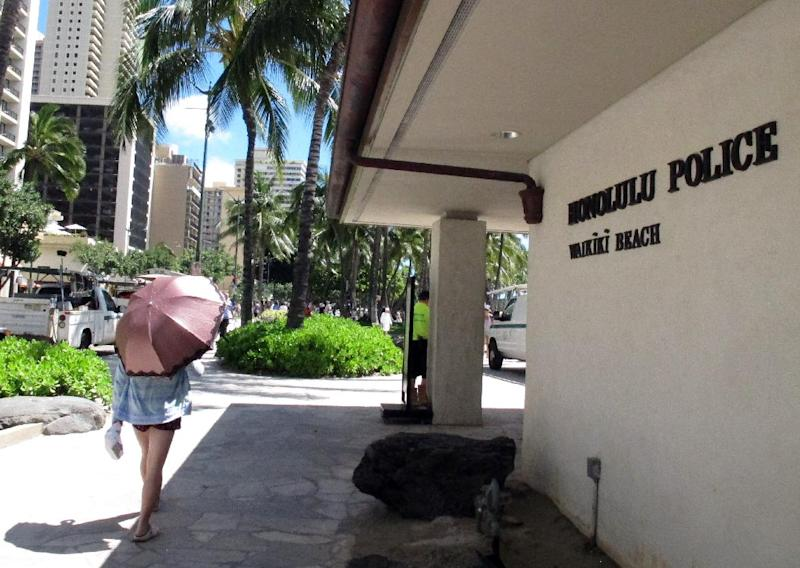 A pedestrian walks in front of a Honolulu Police Department station in Honolulu's tourist area of Waikiki on Wednesday, March 19, 2014. As Hawaii lawmakers considered a measure that would crack down on prostitution, the Honolulu Police Department requested a change that has shocked human trafficking experts and victims rights advocates: Police wanted it to remain legal for undercover officers to have sex with prostitutes. (AP Photo/Oskar Garcia)