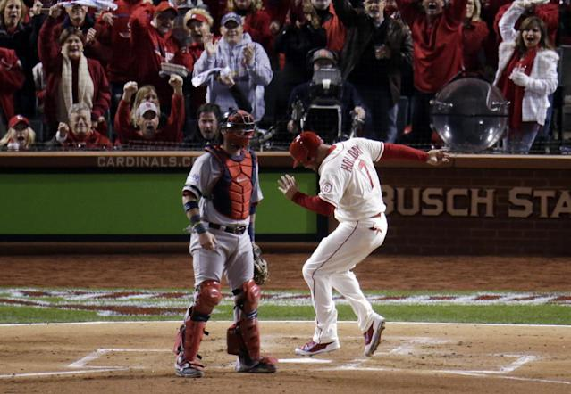 St. Louis Cardinals' Matt Holliday (7) scores past Boston Red Sox catcher Jarrod Saltalamacchia during the first inning of Game 3 of baseball's World Series Saturday, Oct. 26, 2013, in St. Louis. (AP Photo/Charlie Riedel)