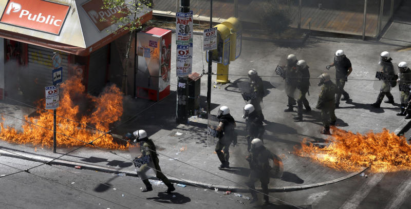 A fire bomb explodes among riot police during clashes in Athens Wednesday Sept. 26, 2012. Police clashed with protesters hurling petrol bombs and bottles in central Athens Wednesday after an anti-government rally called as part of a general strike in Greece turned violent.  (AP Photo/Dimitri Messinis)