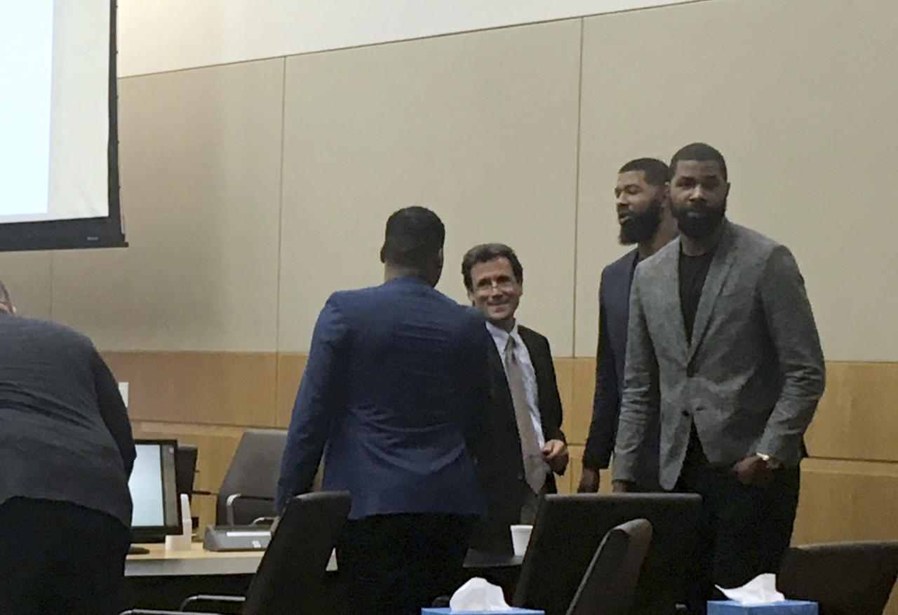 "From left, Gerald Bowman, defense attorney Jim Belanger, Markieff Morris and Markieff Morristalk appear in the courtroom following opening statements made by attorneys Monday, Sept. 18, 2017, in Phoenix. The NBA players went on trial Monday on felony assault charges stemming from a 2015 beating that prosecutors labeled as an ""orchestrated attack"" and defense lawyers dismissed as a ploy to get money out of the athletes. (AP Photo/Clarice Silber)"