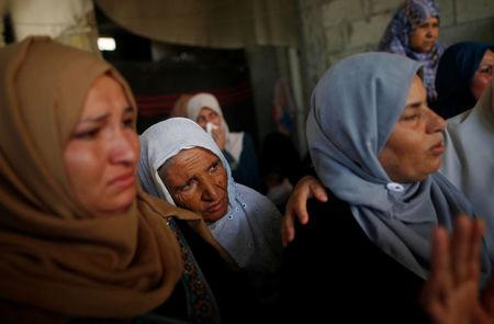 Relatives mourn during the funeral of a Palestinian, who was killed during a protest at the Israel-Gaza border, in the central Gaza Strip May 16, 2018. REUTERS/Mohammed Salem