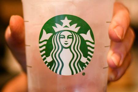 A employees poses with a cup of water at a Starbucks coffeehouse in Austin, Texas