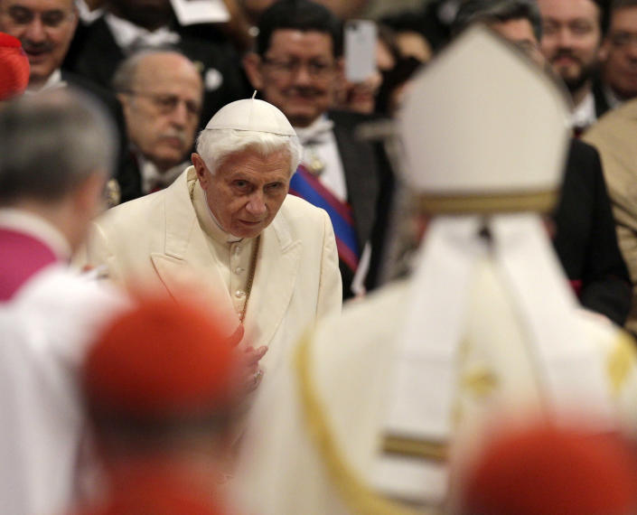 Pope Emeritus Benedict XVI bows as Pope Francis, right with back to camera, arrives for a consistory inside the St. Peter's Basilica at the Vatican, Saturday, Feb.22, 2014. Benedict XVI has joined Pope Francis in a ceremony creating the cardinals who will elect their successor in an unprecedented blending of papacies past, present and future. (AP Photo/Alessandra Tarantino)
